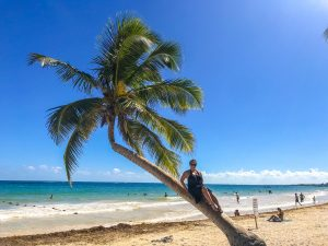 Me sitting on a palm tree at Playa Paraiso